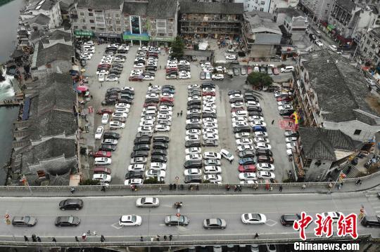 古城内一停车场停满了自驾游的私家车。 杨华峰 摄