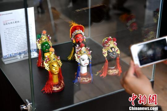 图为福建木偶雕刻艺术品吸引市民拍照。 吕明 摄