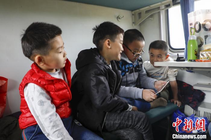 图为在3274次列车上,孩子们在一起看动漫。 高晋 摄